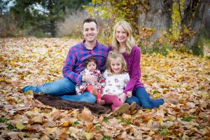 a portrait of my family and I sitting in fall leaves