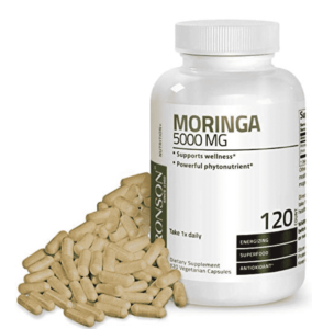 moringa capsules piled next to a pill bottle