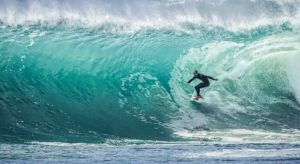 a surfer rides a huge wave with energy he got from coconut oil