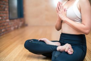 a woman meditates as part of her yoga routine