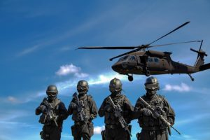 4 members of the military police with a helicopter in the background