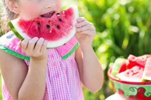 a kid eating watermelon