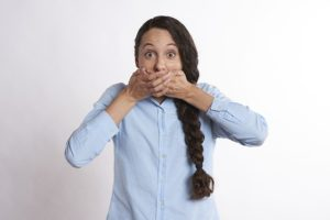 a woman covering her mouth because she just ate some unhealthy food