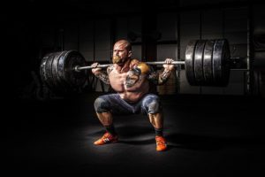 a weight lifter pushes himself harder for better weight loss results