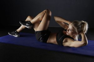 a woman does crunches on a purple mat