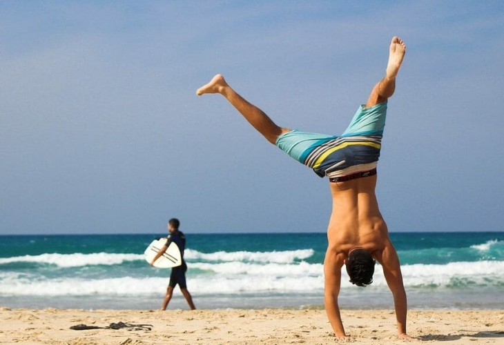 a man does a cartwheel on the beach after losing a lot of weight