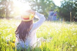 a woman sits in a field, happy to finally be candida free