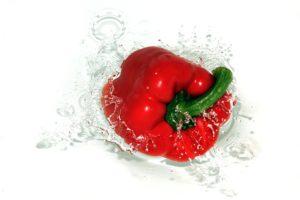 a bell pepper splashing in water
