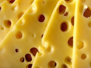 a pile of swiss cheese too much dairy can quickly derail your keto diet plan