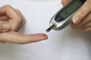a person checks their bloodsugar after having a glass of red wine
