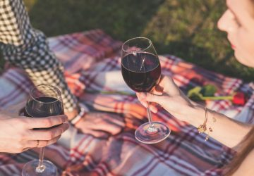 a young couple enjoys red wine on a picnic blanket