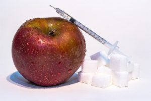 an insulin syringe perched on top of an apple and sugar cubes
