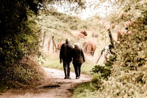 an elderly couple walks to the wine shop
