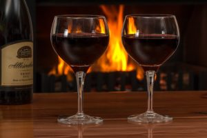 two glasses of shiraz in front of the fire