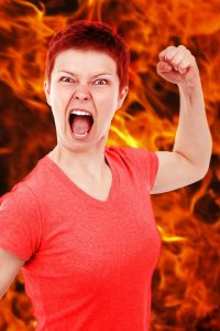a very angry woman raises her fist with flames behind her