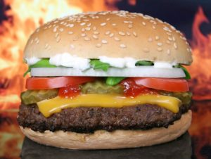 a cheesburger sits with flames behind it