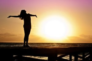 a very happy woman stands facing the sun
