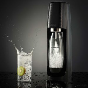 a class of sparkling water next to a soda stream