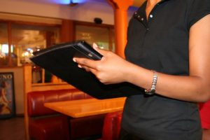 a waitress takes a person's order