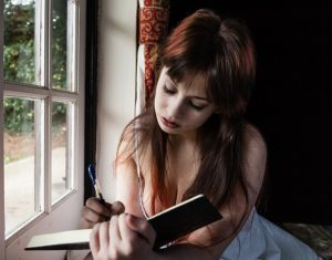 a woman writes in her food journal