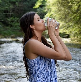 a woman takes her pills with a big glass of water