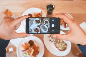 a person takes a picture of their  restaurant food