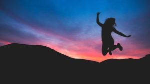a woman jumps in the sunset