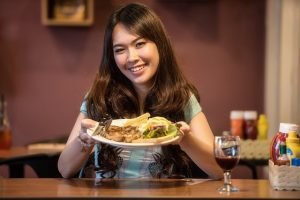 a woman gets ready to eat a meal with steak as the main dish