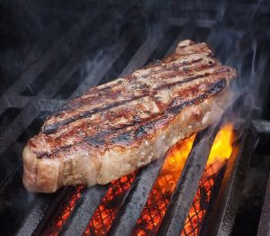a steak cooks on the grill